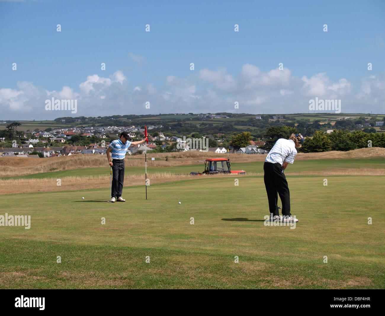 Two teenage boys playing golf, Bude, Cornwall, UK 2013 - Stock Image