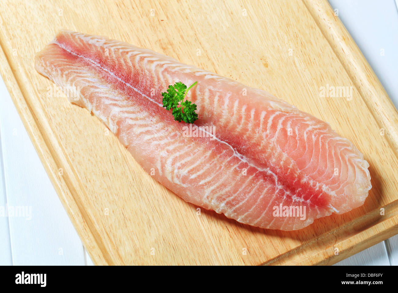 Frozen catfish fillet on cutting board - Stock Image