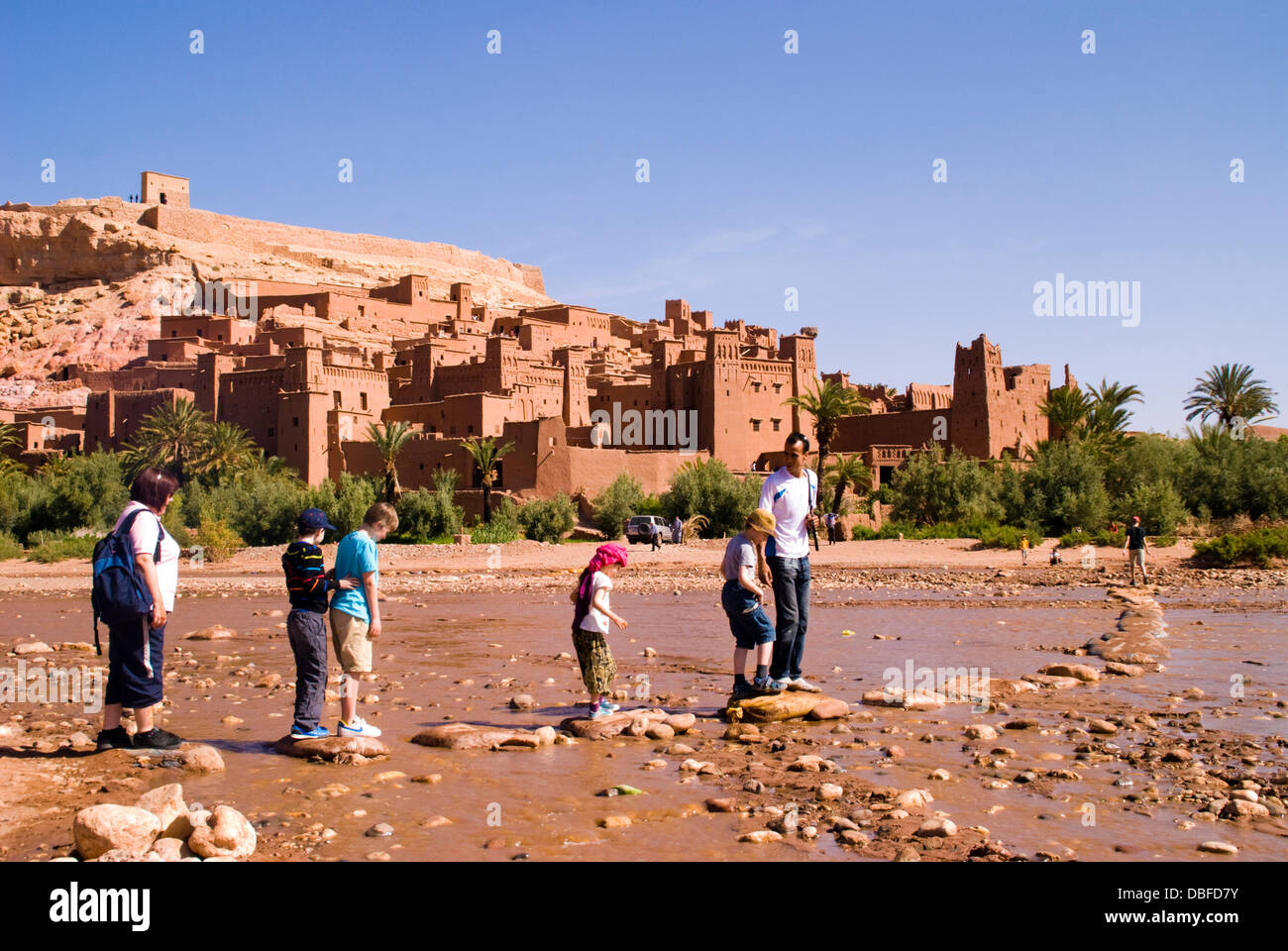 Aït Benhaddou in Berber Ath Benhadu . Young tourists cross the Ounila River Most of the town's inhabitants - Stock Image