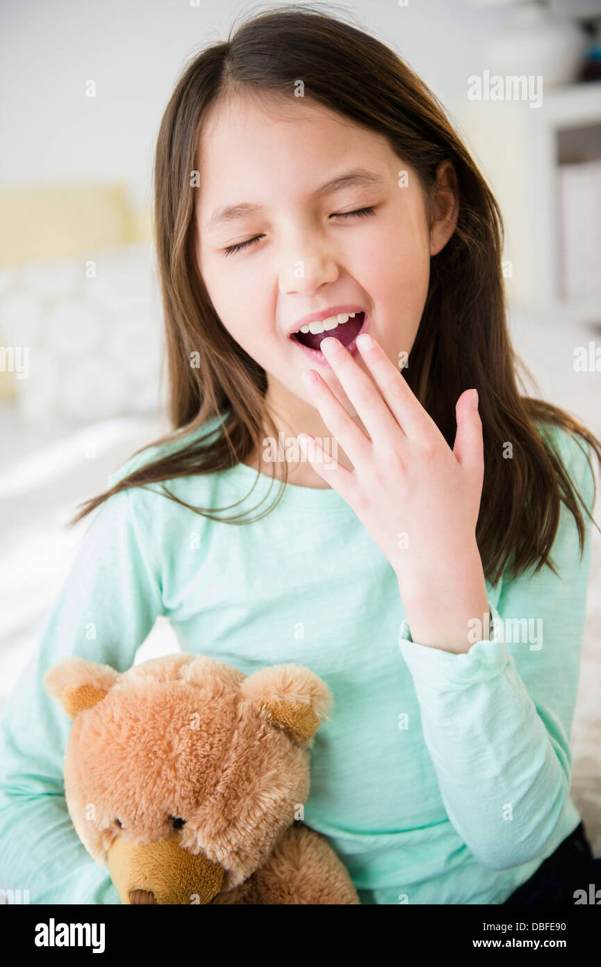 Mixed race girl with teddy bear yawning Stock Photo