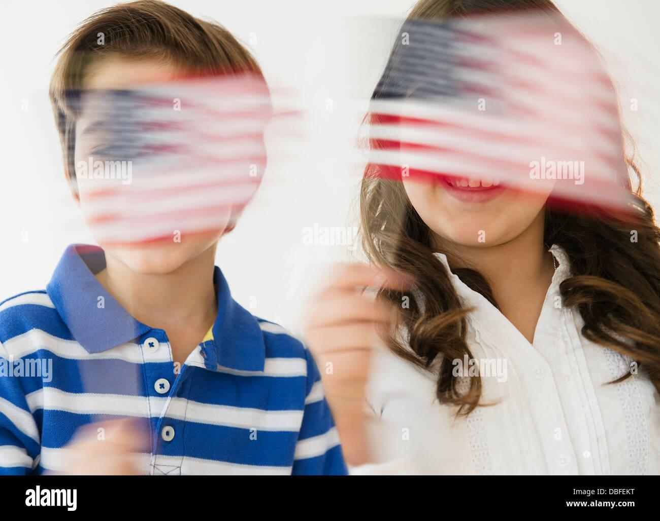 Hispanic children waving American flags Stock Photo