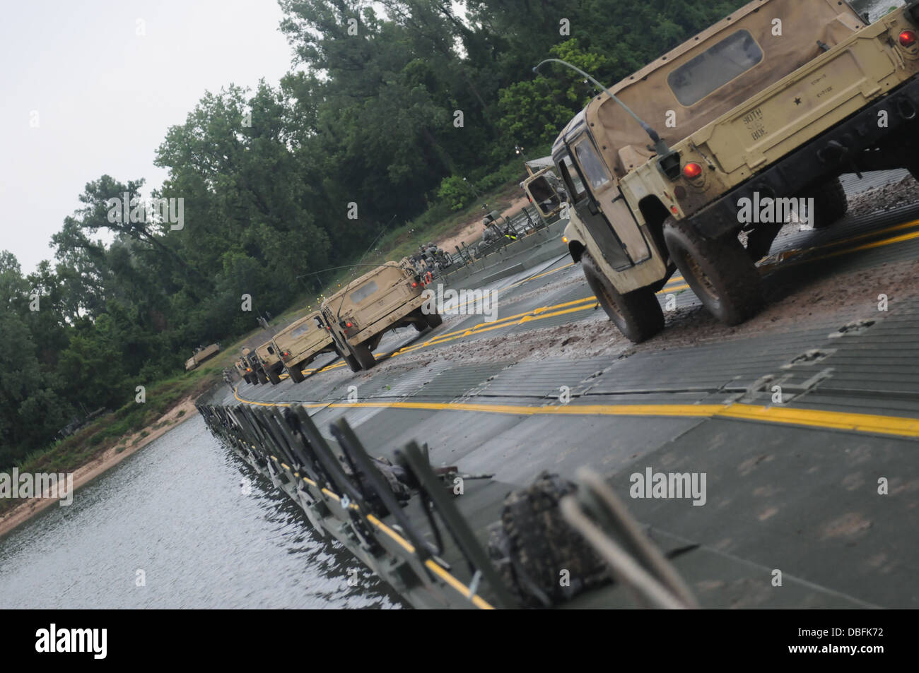 A security element convoy travels across a finished Improved Ribbon Bridge during Operation River Assault July 24, - Stock Image