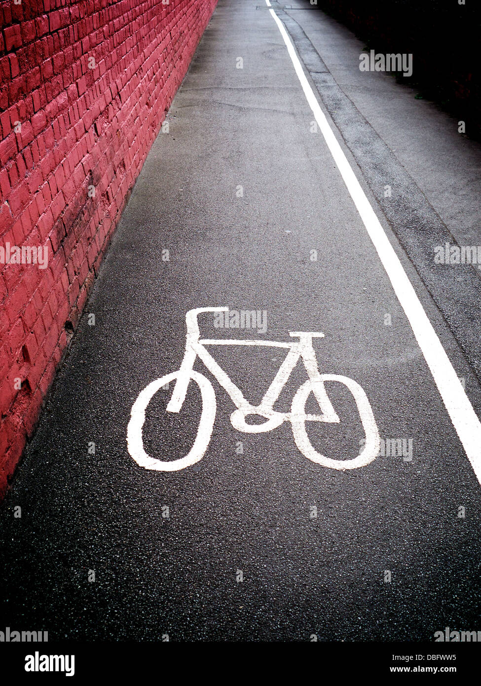 Cycle path symbol on a British sidewalk pavement with a solid white line separating the cycle path from the pedestrian - Stock Image