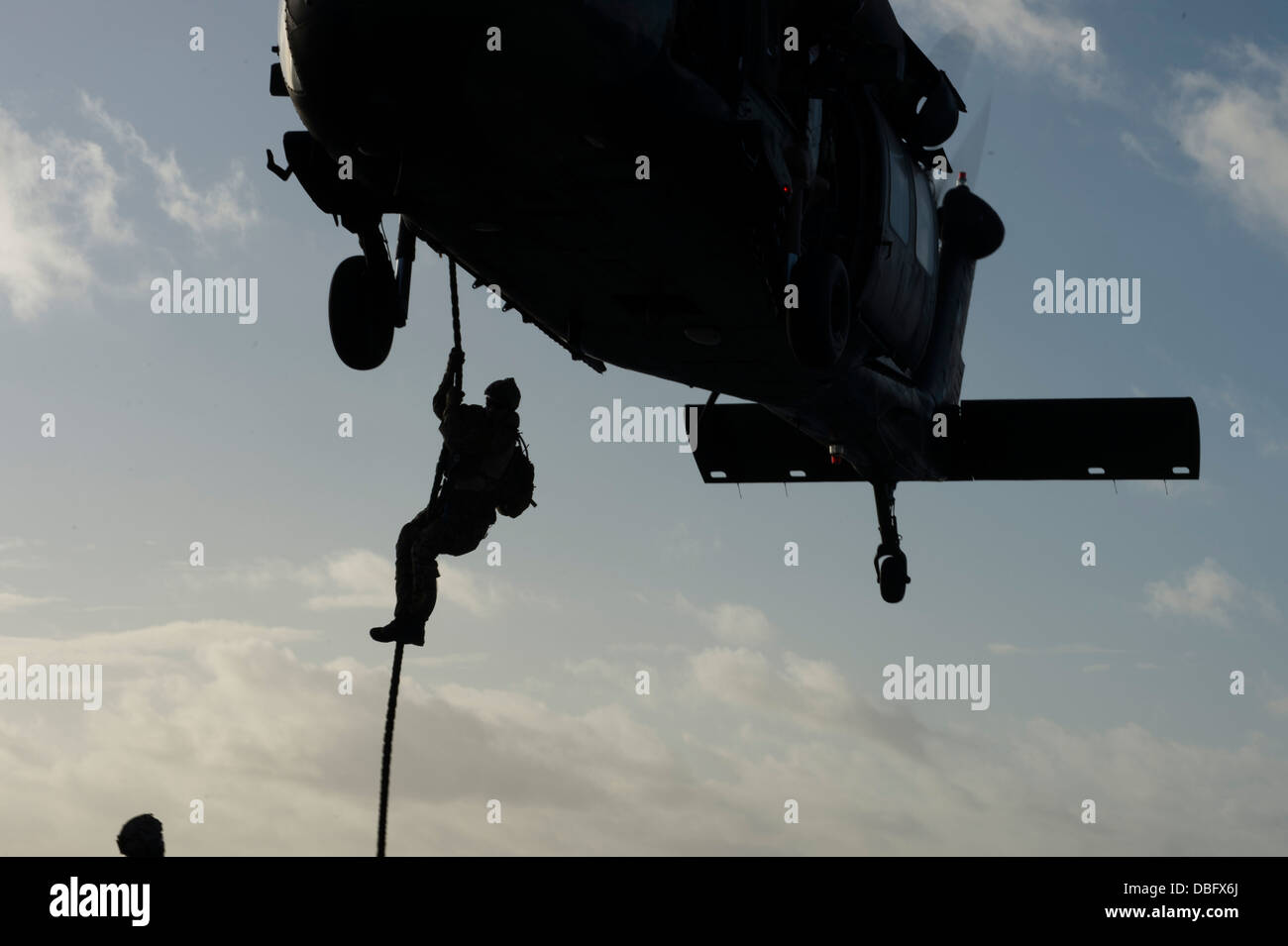 An Australian army soldier from the 2nd Commando Regiment, Domestic Counter Terrorism fast-rappels from a S-70A Stock Photo