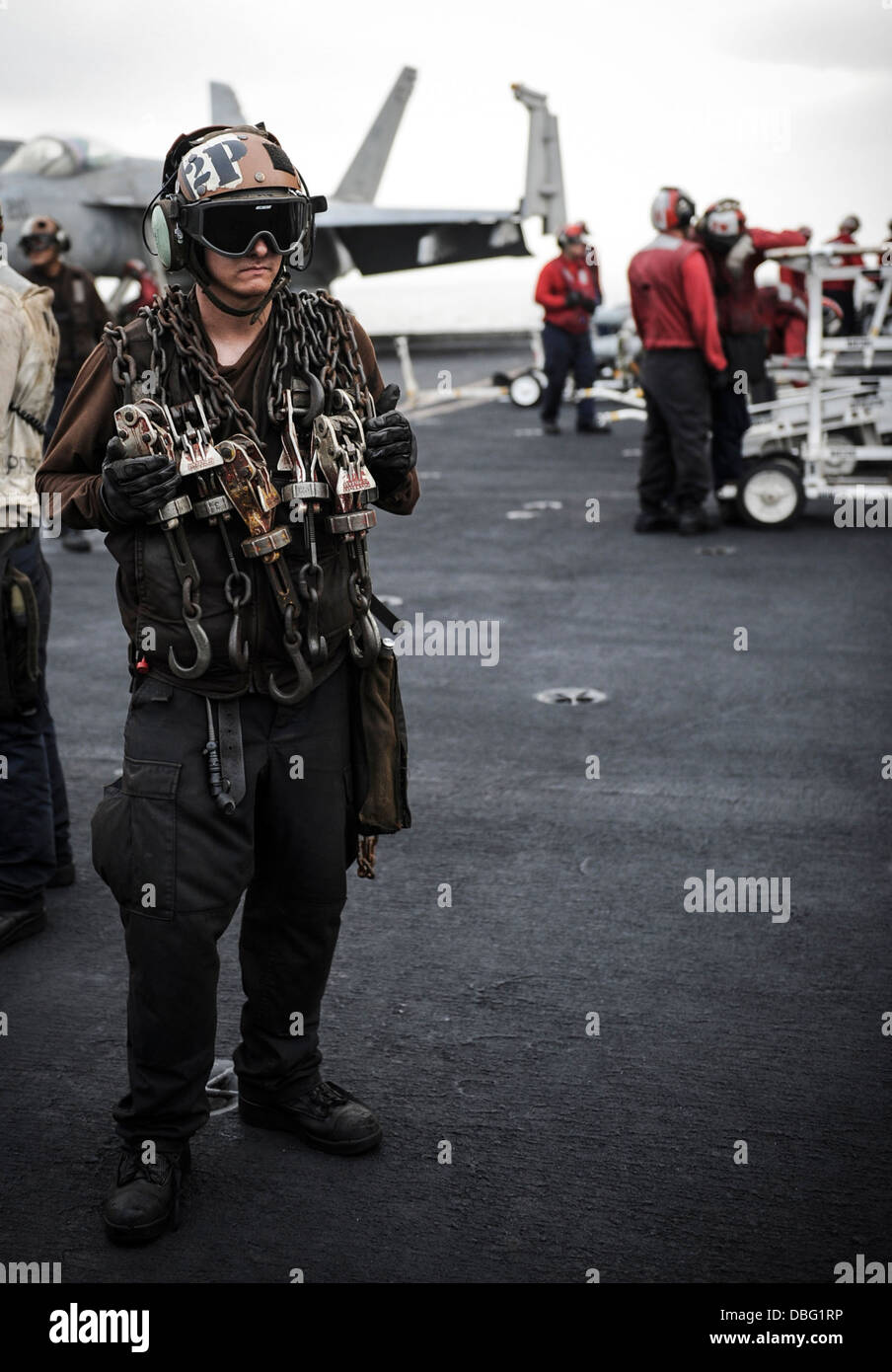 us navy aviation machinists mate 2nd class forrest sledge assigned to strike fighter squadron vfa 147 stands by with chains on the flight deck of the
