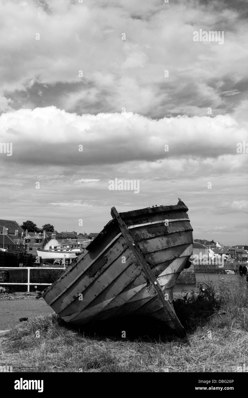 Black and white image of an old boat lying on grass near a harbour with cloudy sky - Stock Image