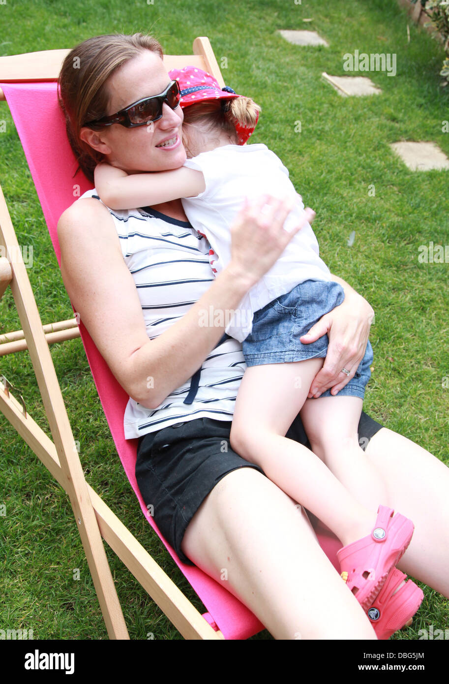 Mum comforting her child while sitting in a deckchair. - Stock Image