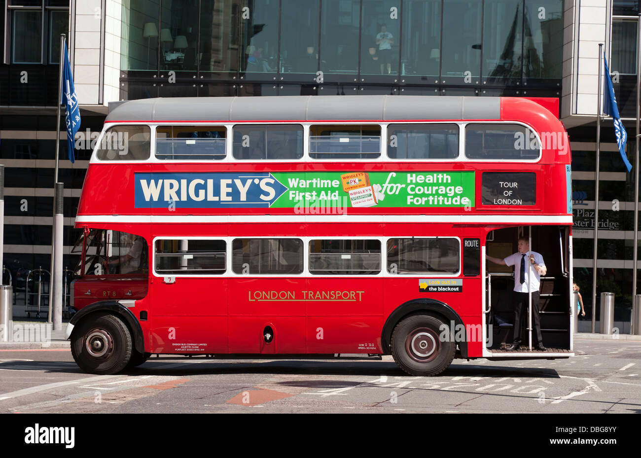 A restored pre-war, London RT bus, being used for tours of London, passes infront of the Park Plaza Hotel. - Stock Image