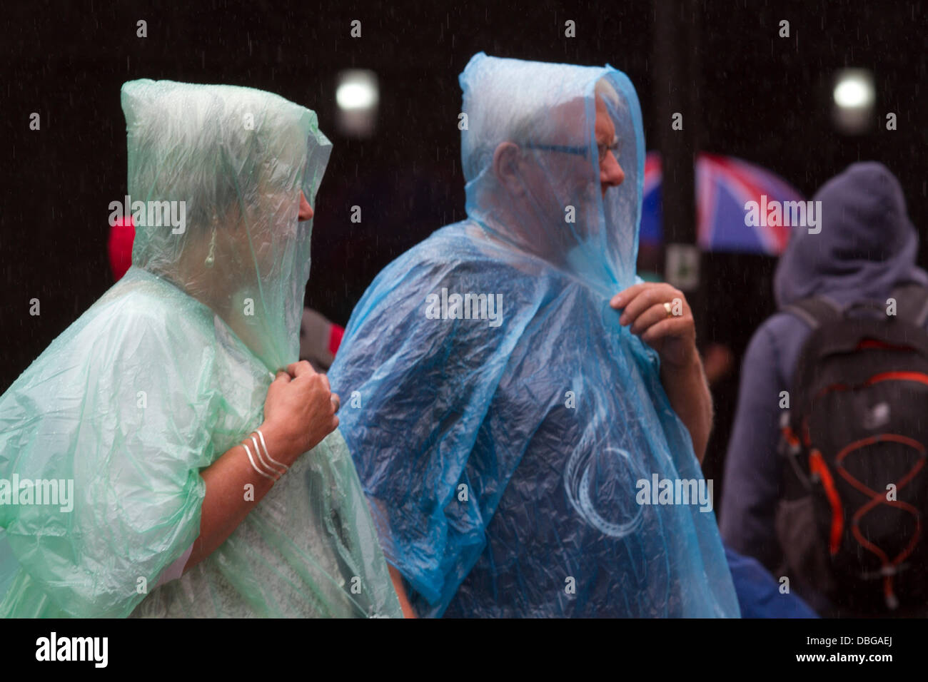 London UK. 30th July 2013.Tourists in Piccadilly circus in rain ponchos as London is hit with heavy downpours after - Stock Image