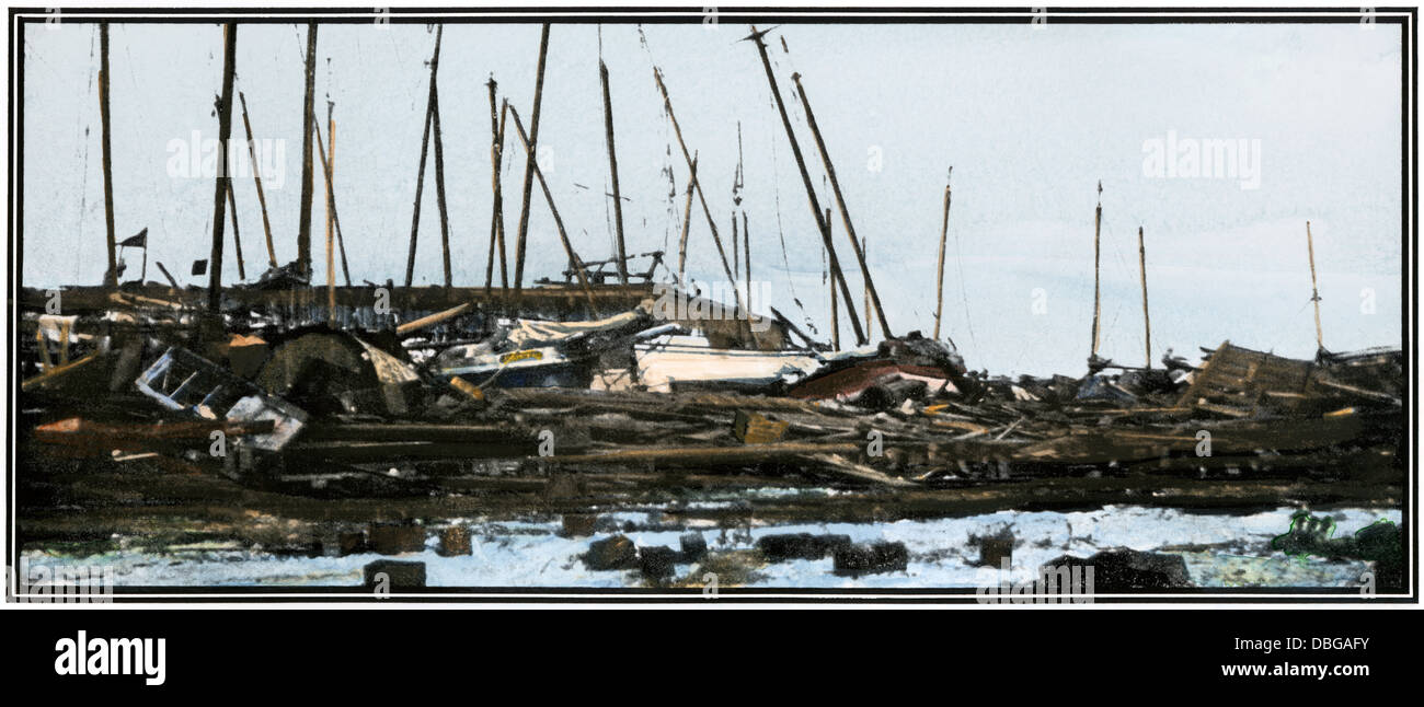 Oyster boats piled up at a Galveston wharf after the hurricane of 1900. Hand-colored halftone reproduction of a - Stock Image