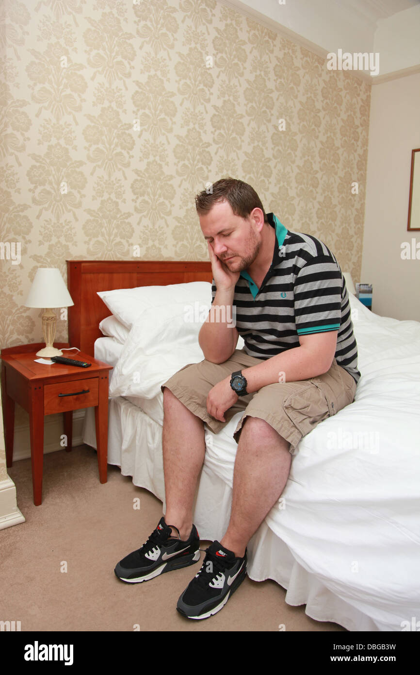 Man in hotel bedroom stressed and upset. - Stock Image