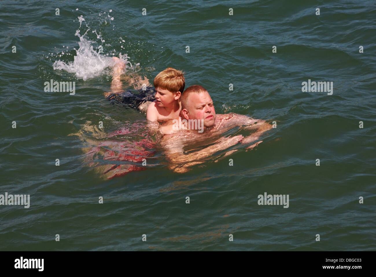 young lad holding onto man and kicking his legs to splash in the sea at Swanage in July - Stock Image