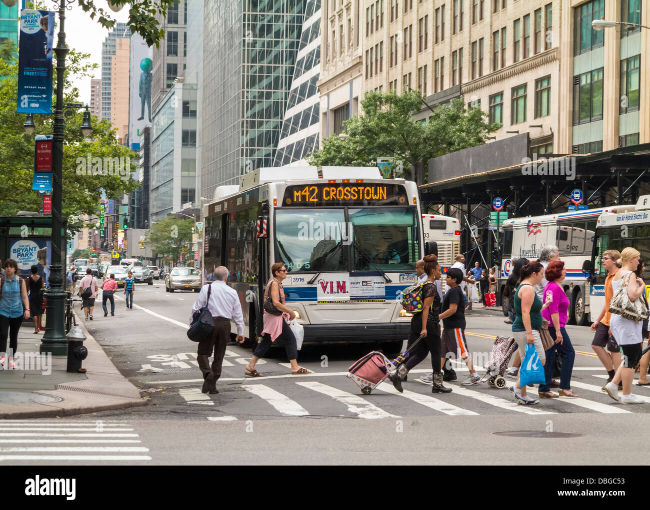 Bus at crosswalk road junction on a city street in Manhattan, New York City - Stock Image