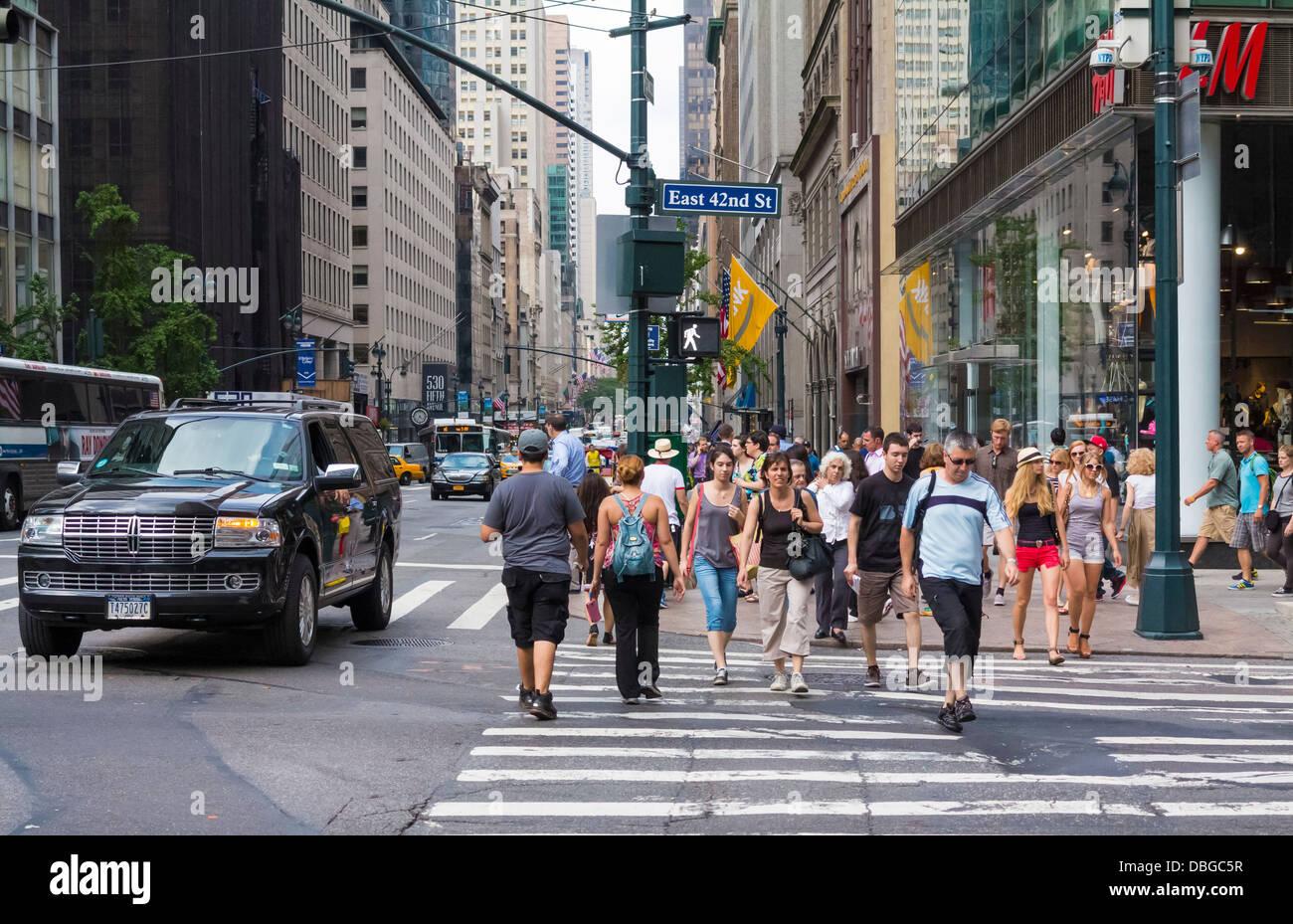 Manhattan New York street scene - people walking across a downtown crosswalk in Manhattan, New York City in summer - Stock Image