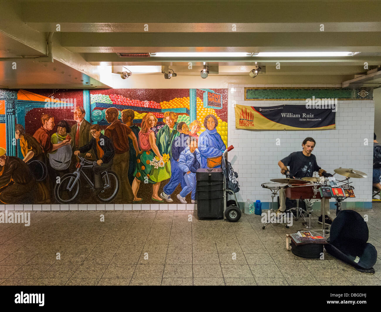 Busker street performer in the New York Subway next to a large mosiac - Stock Image