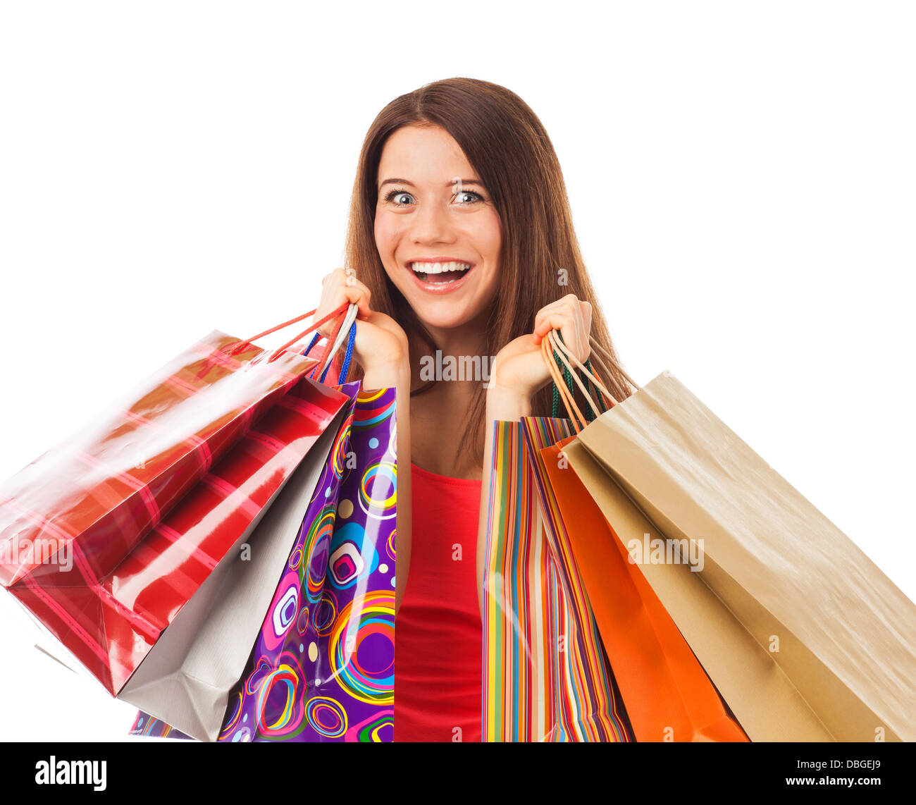 Portrait of a young woman holding shopping bags and looking very happy, isolated on white - Stock Image