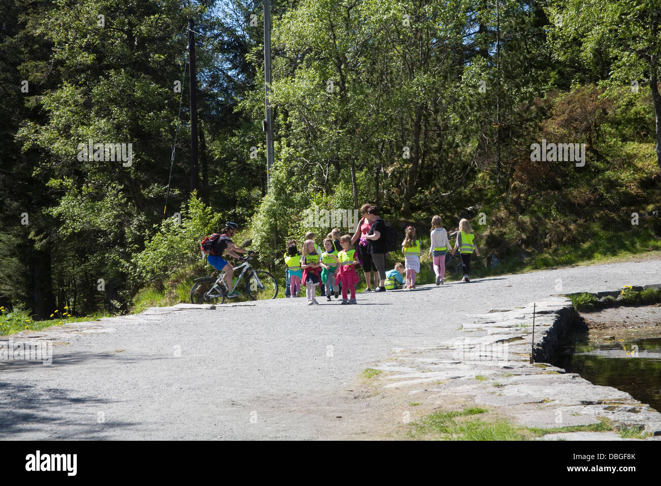 Bergen Norway Europe Group of young schoolchildren teachers and male mountain biker on one of Mount Floyen trails - Stock Image