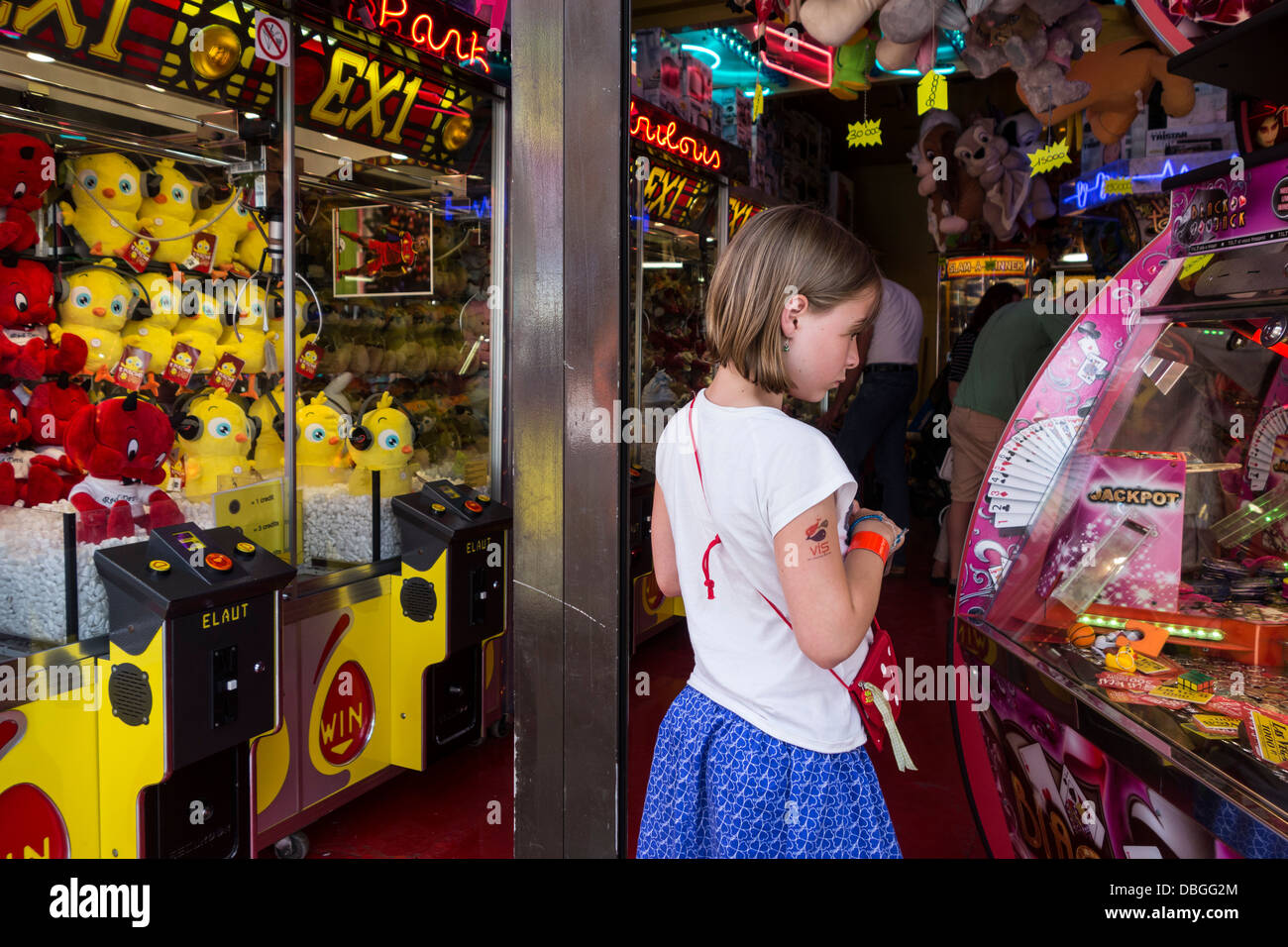 Arcade with claw crane game machines and child looking at coin pusher / push medal game at travelling funfair / - Stock Image