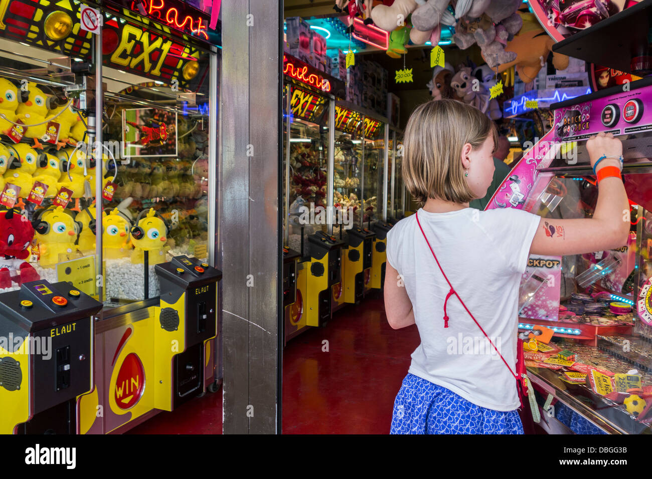 Arcade with claw crane game machines and child playing with coin pusher / push medal game at travelling funfair - Stock Image