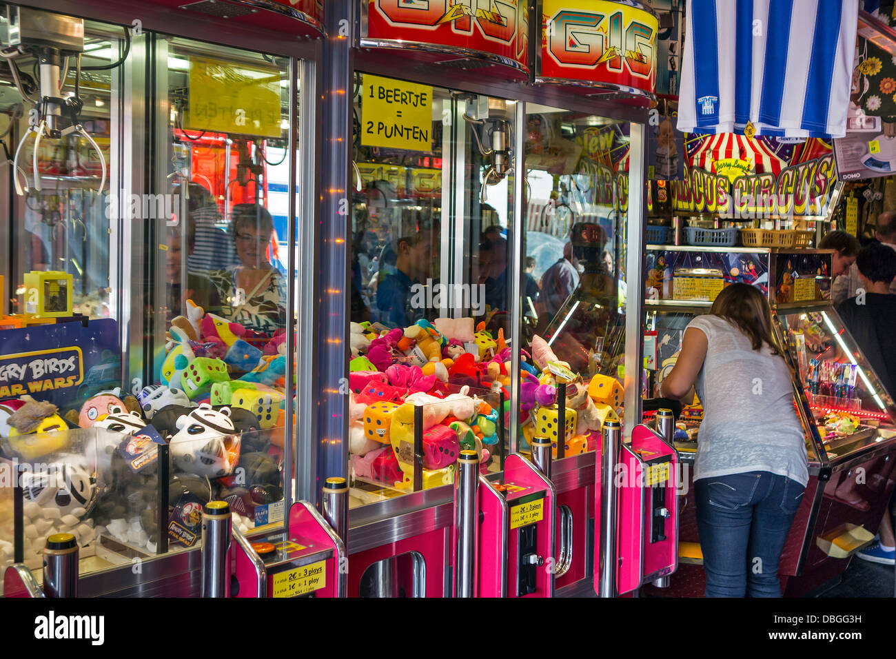 Arcade with claw crane game machines filled with toys and coin pusher / push medal games at travelling fun fair - Stock Image