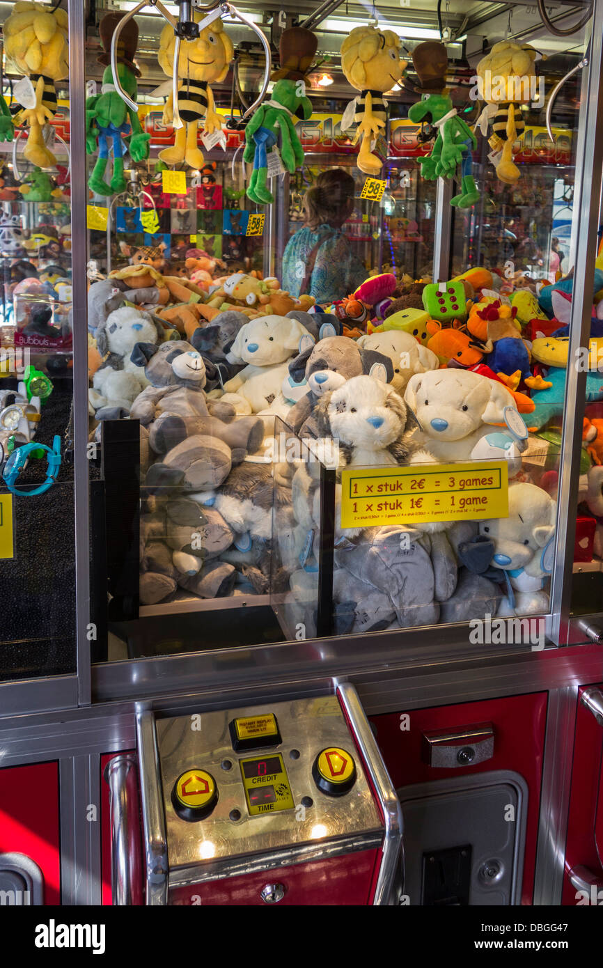 Arcade with claw crane game machines filled with toys at travelling funfair / traveling fun fair - Stock Image