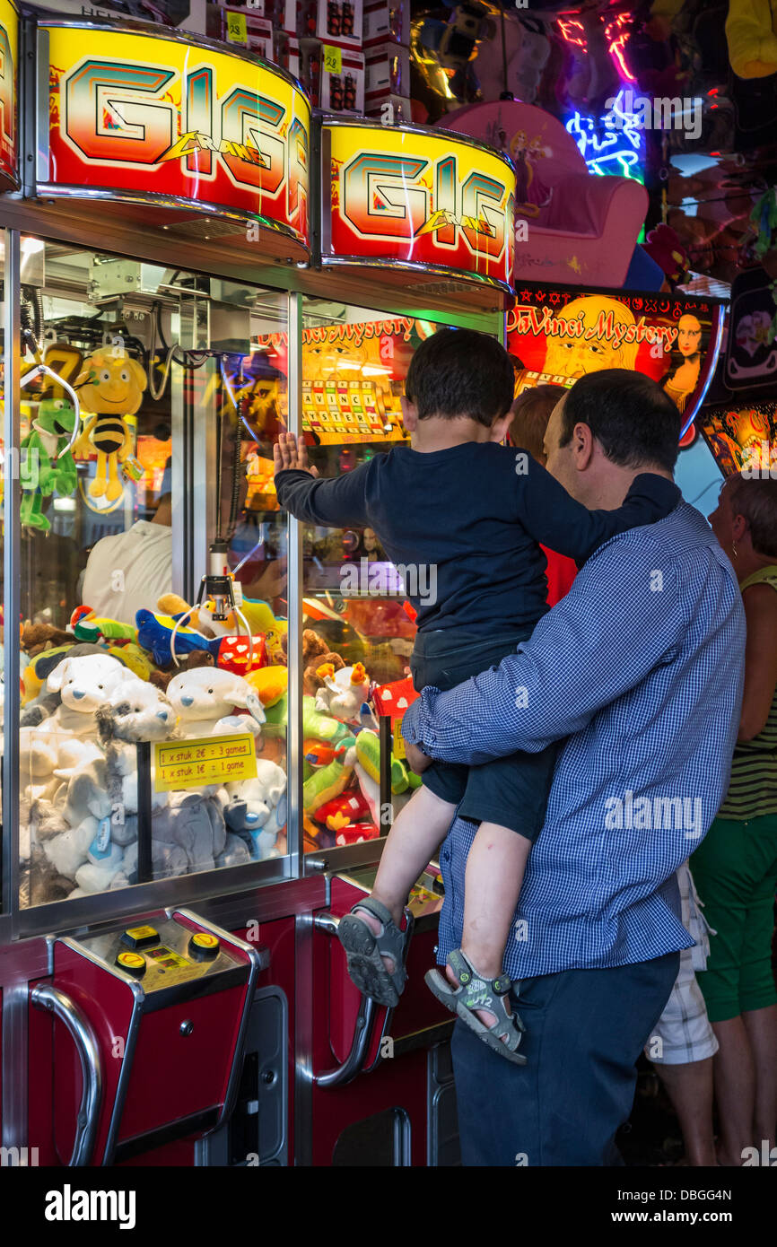 Father with son looking at claw crane game machine filled with toys in amusement arcade at traveling funfair / fun - Stock Image