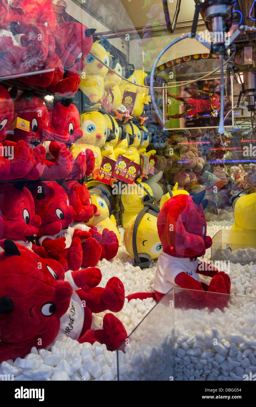 Amusement arcade with claw crane game machines filled with colourful toys at travelling funfair / traveling fun - Stock Image