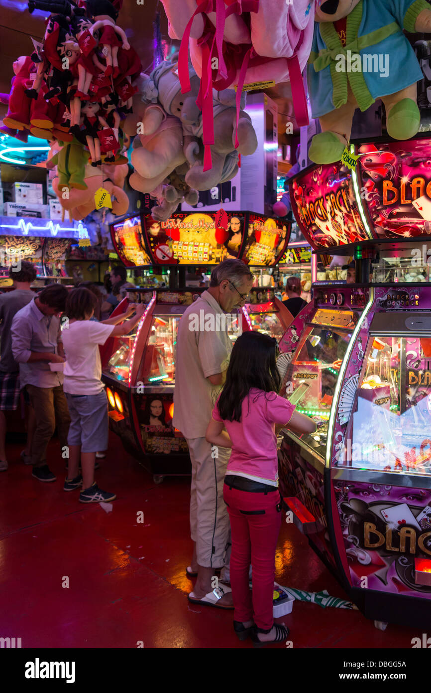Father with girl playing with coin pusher / push medal game in amusement arcade at travelling funfair / traveling - Stock Image
