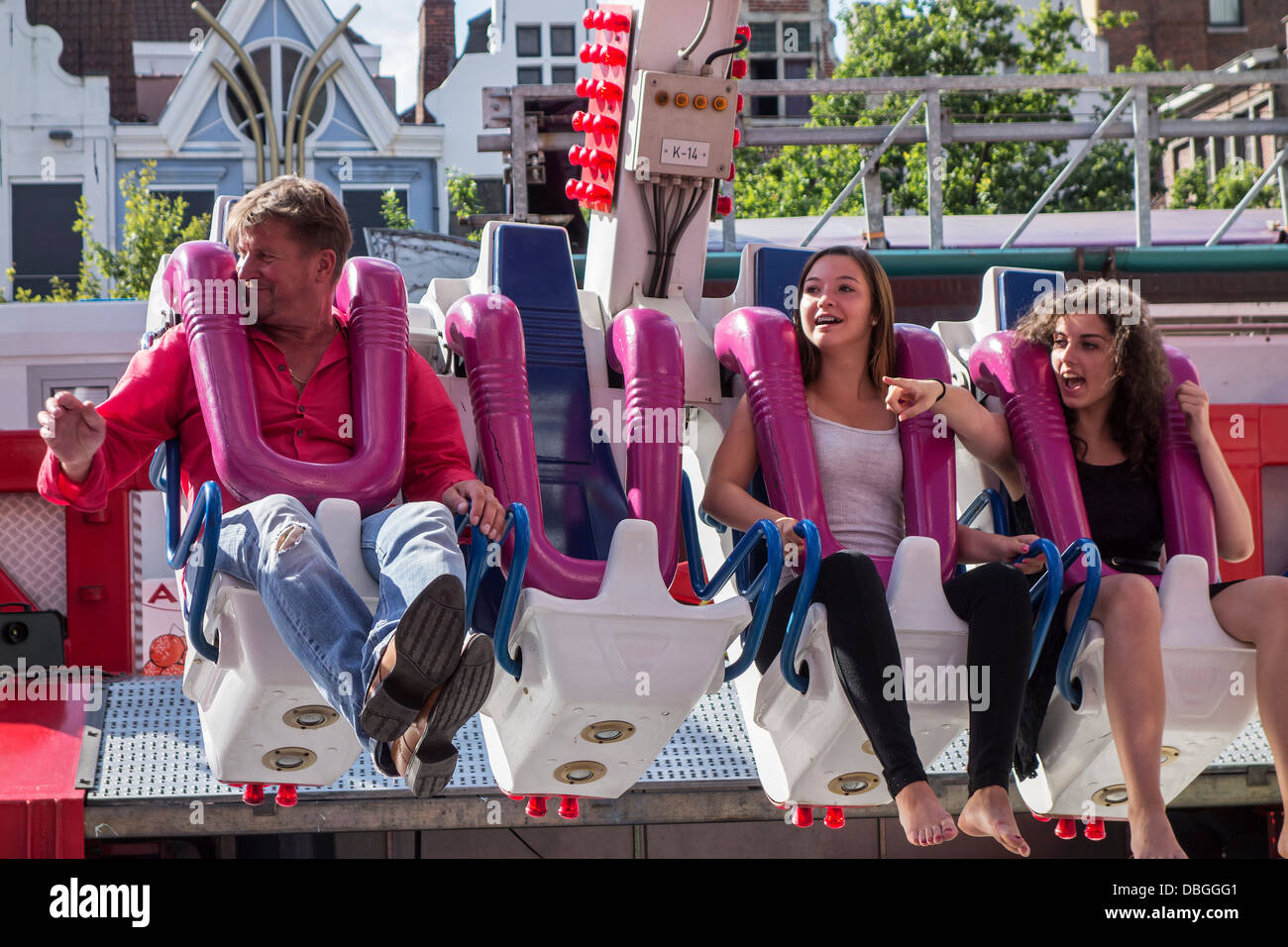 Excited and cheerful thrill seekers having fun on the fairground attraction G Force at travelling funfair / traveling - Stock Image
