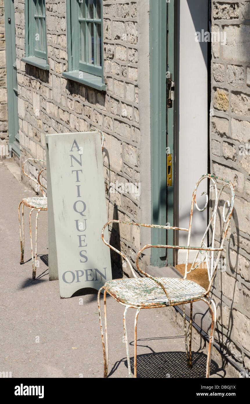 Sign For Antiques Shop And An Old Metal Chair On The Pavement In Tetbury    Stock