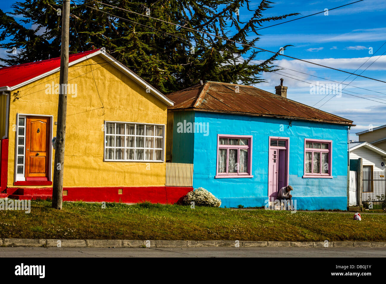 Person sitting on doorstep of a brightly coloured houses in vivid Punta Arenas Chile & Person sitting on doorstep of a brightly coloured houses in vivid ...