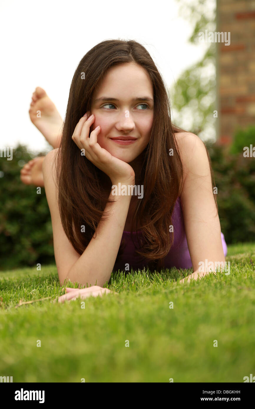 brunette tween girl laying on stomach - Stock Image