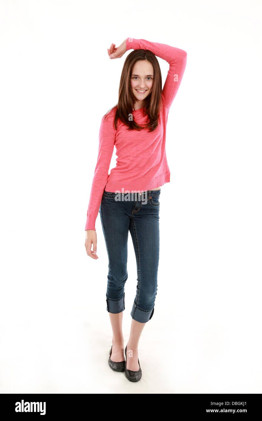 full length of thin brunette tween girl smiling - Stock Image
