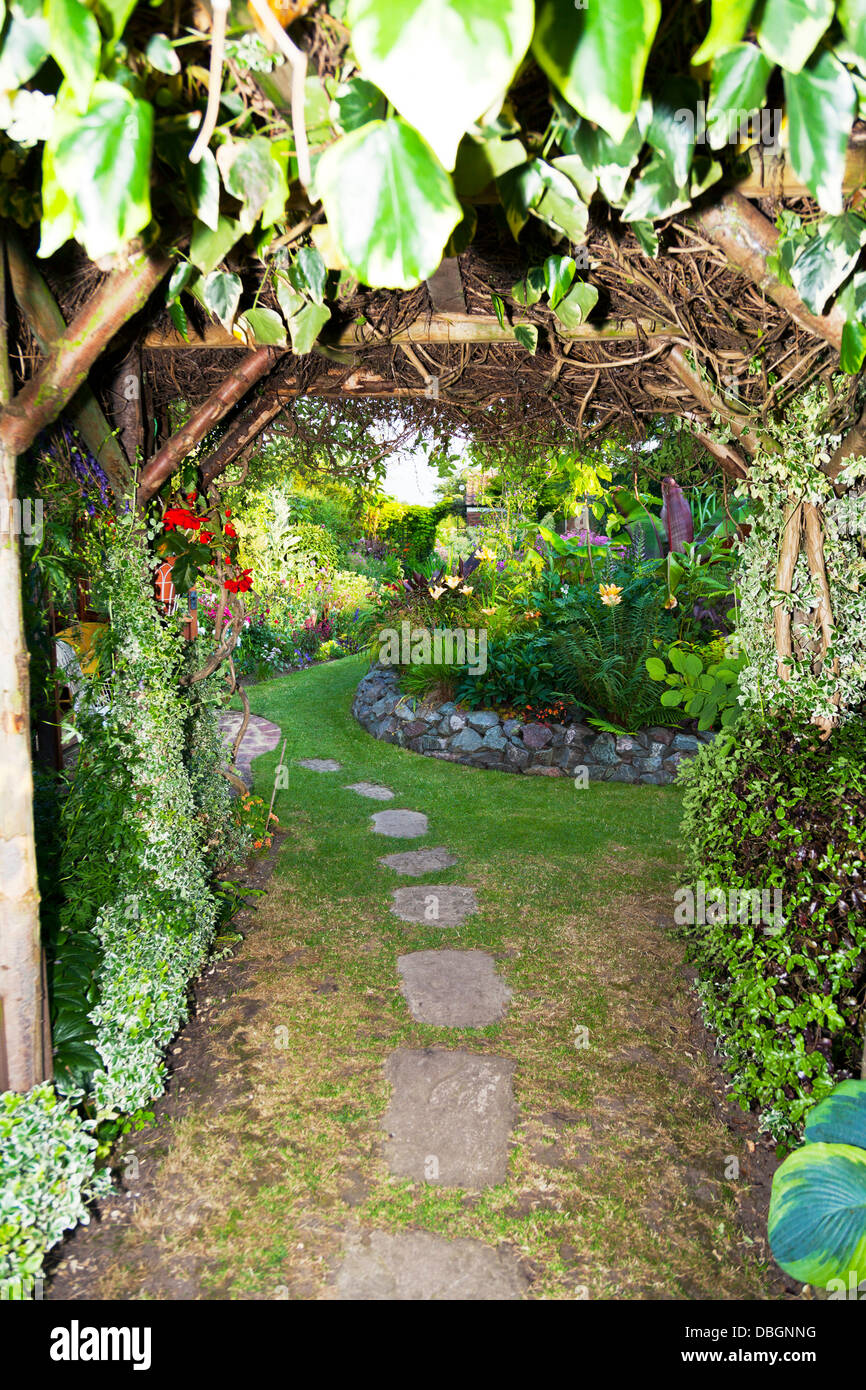 Typical English garden Arbour Arch archway Canopy leading in to garden Stock Photo