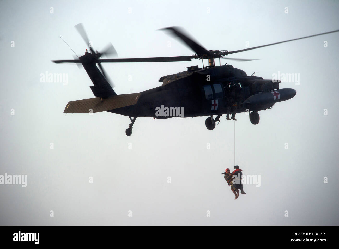 A US Army Flight Medic retrieves a Green Beret special forces soldier using a hoist to a UH-60 Blackhawk helicopter Stock Photo