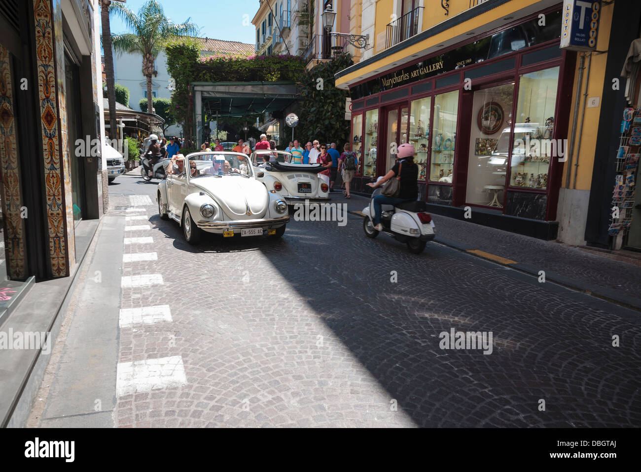 Tourists get a ride through the streets of Sorrento in an open top VW Beetle. - Stock Image