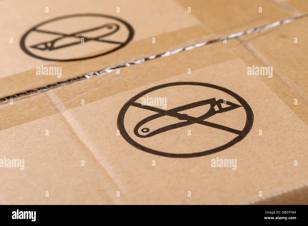 Do not open with a knife sign printed on a cardboard box - Stock Image