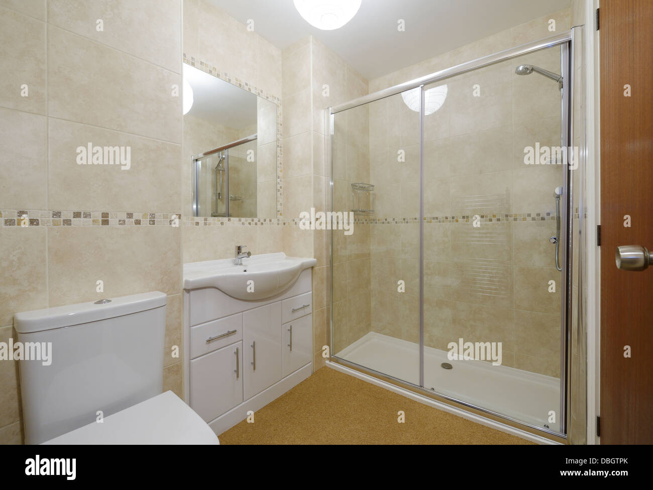 Modern small bathroom with toilet basin and shower - Stock Image