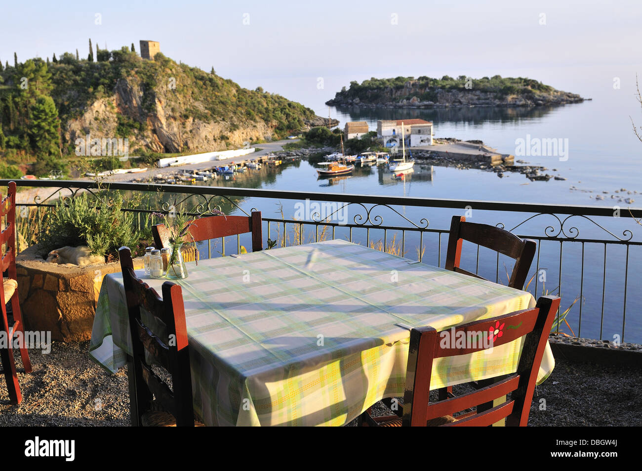 Table in a taverna set  for an evening dinner overlooking the bay in Kardamili,Peloponnese , Greece, Europe - Stock Image