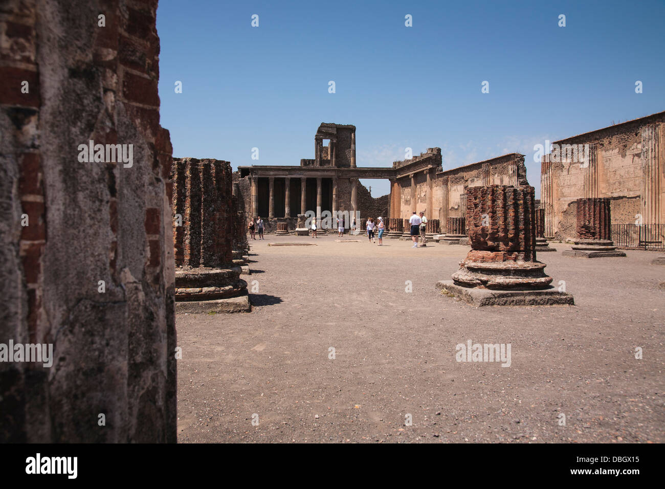 Tourists wander round the ruins of the basilica at Pompeii, Italy. - Stock Image