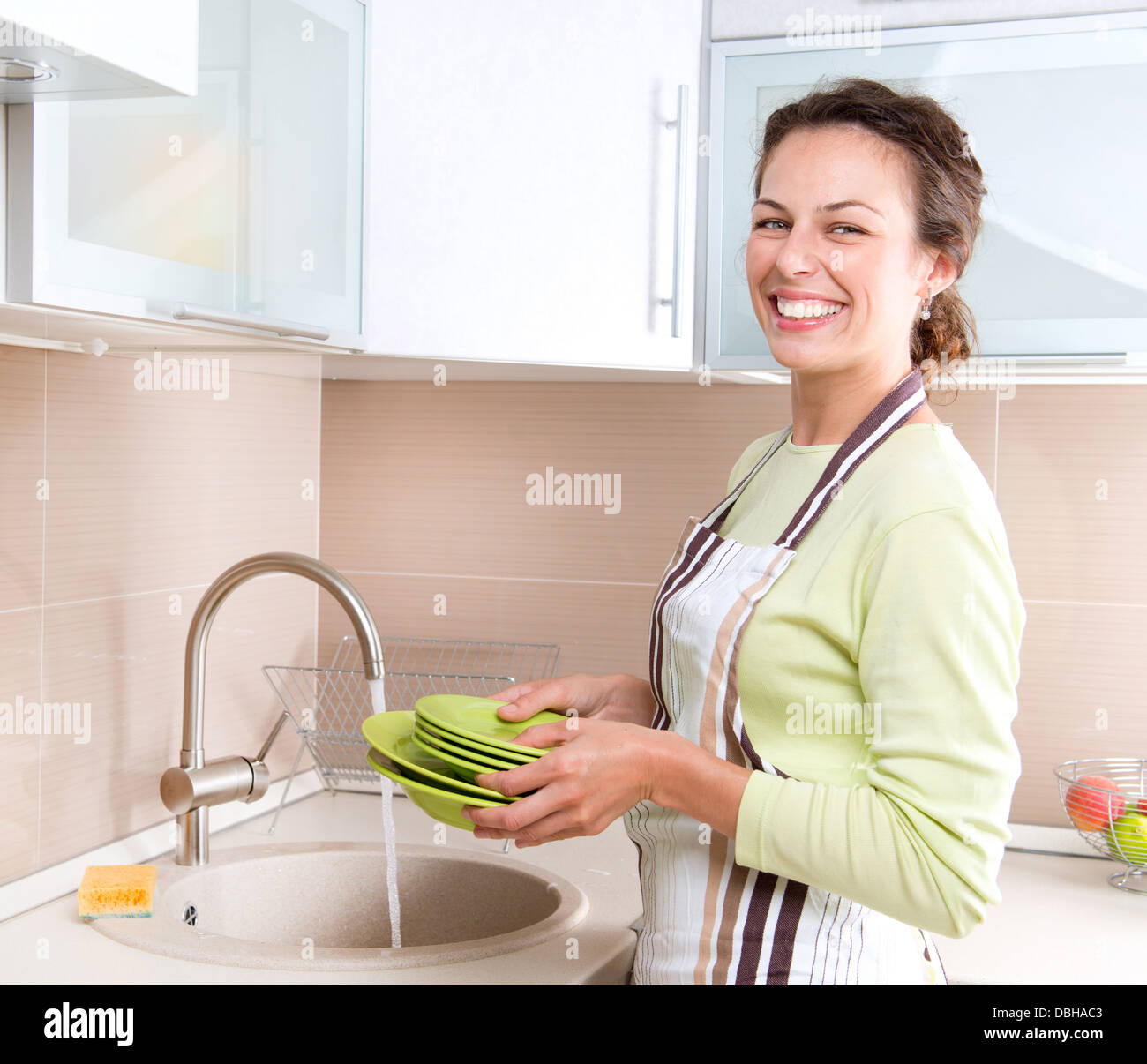 Dishwashing. Happy Young Woman Washing Dishes - Stock Image