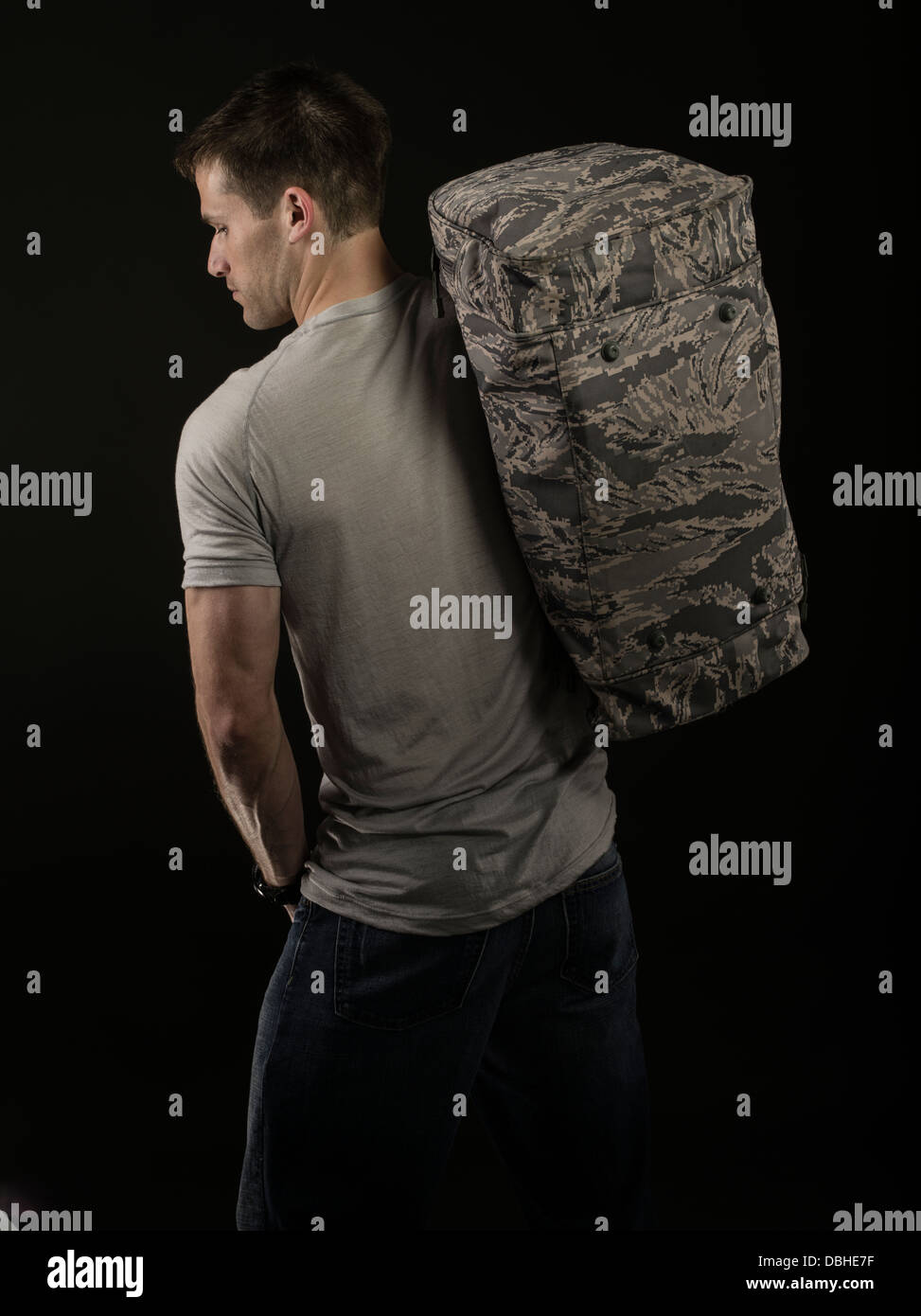 Rugged muscular Caucasian male wearing jeans and grey t-shirt carrying military style bag. Leaving home / work / - Stock Image