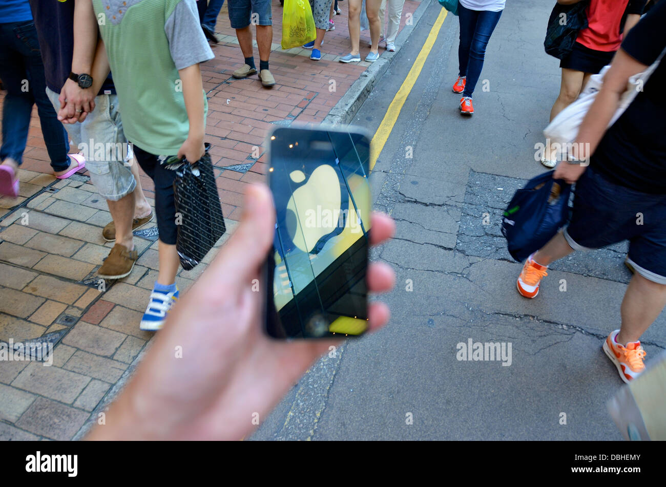 The Apple Store's logo is reflected in the touch screen of an iPhone in Hong Kong. - Stock Image
