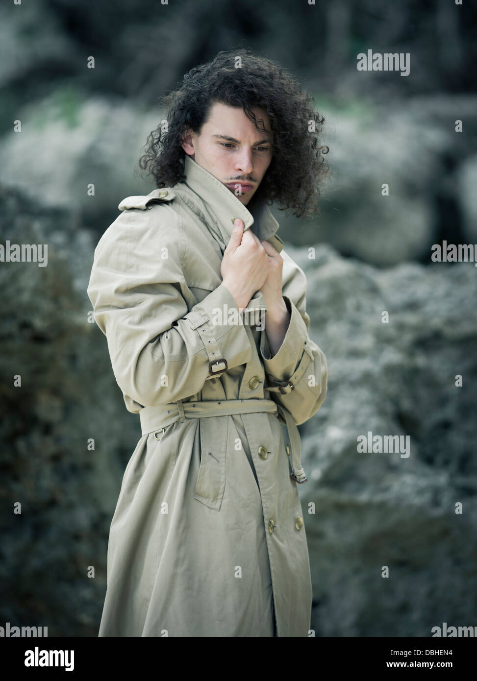 Man with long wavy hair beard and mustache wearing Burberry trench coat  raincoat - Stock Image