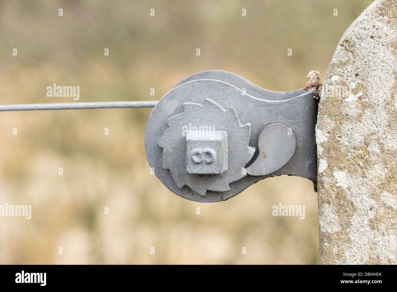 Wire fence tensioner ratchet device mounted on a concrete post and ...
