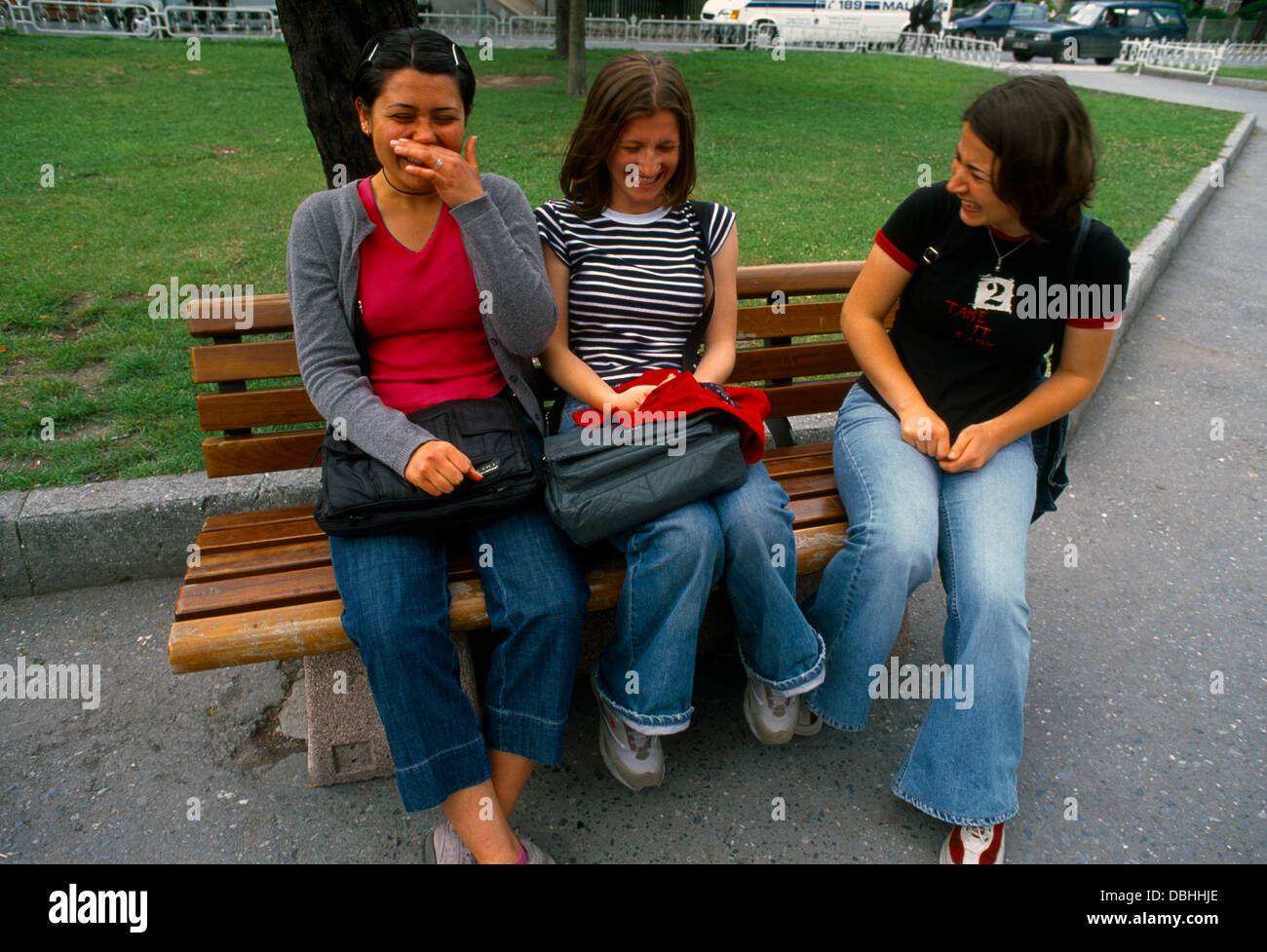 Istanbul Turkey Teenage School Girls Having A Chat Sitting On Park Bench - Stock Image