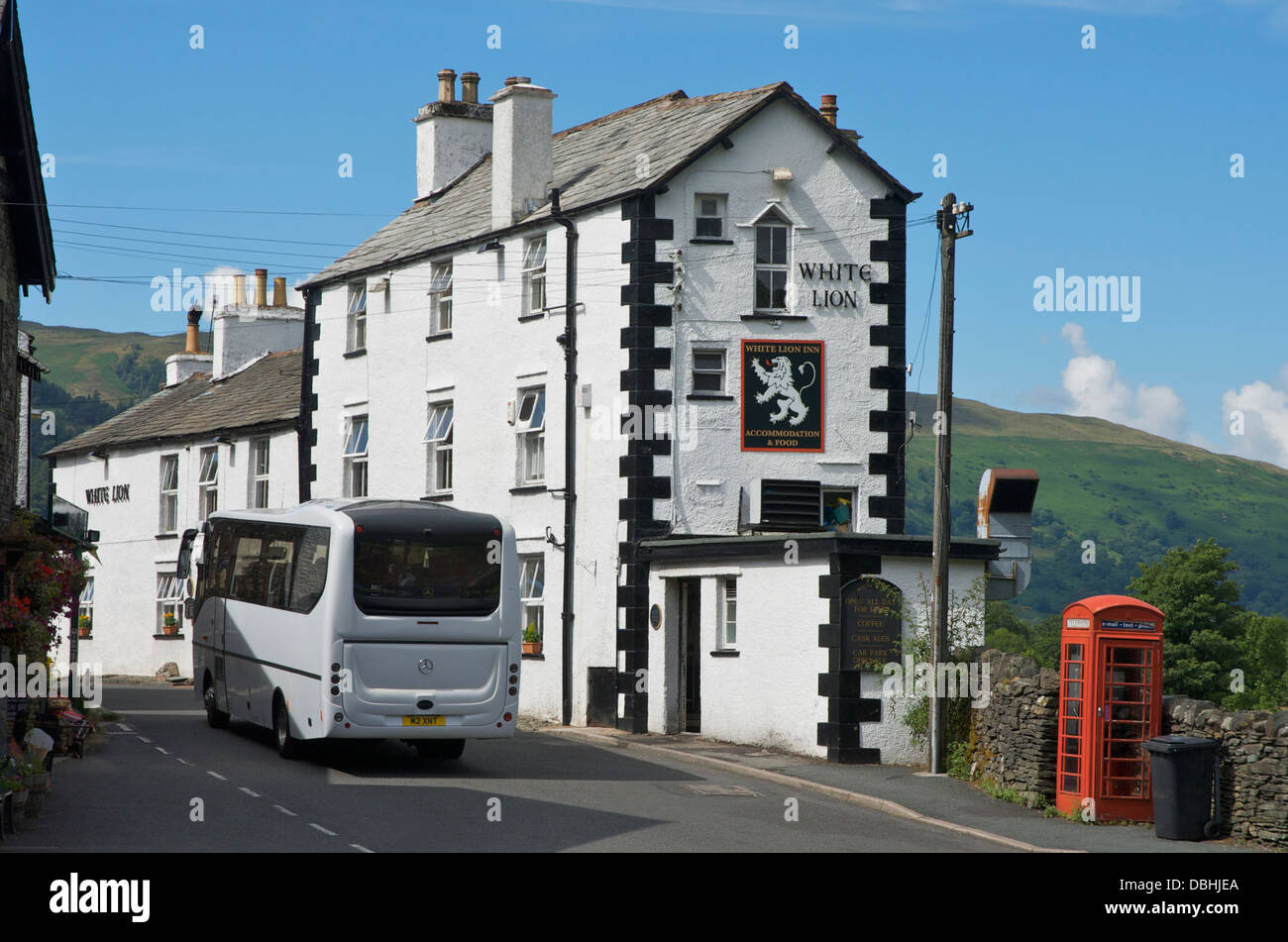 Coach passing the White Lion Inn, Patterdale, Lake District National Park, Cumbria, England UK - Stock Image