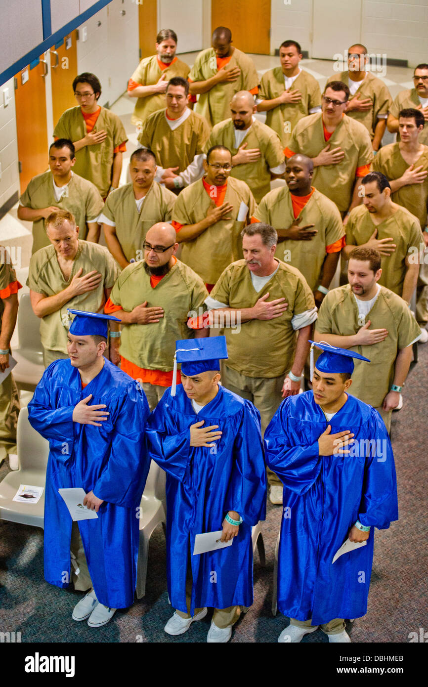 Wearing academic caps and gowns, three inmates are joined by their fellow multiracial prisoners in the city jail - Stock Image