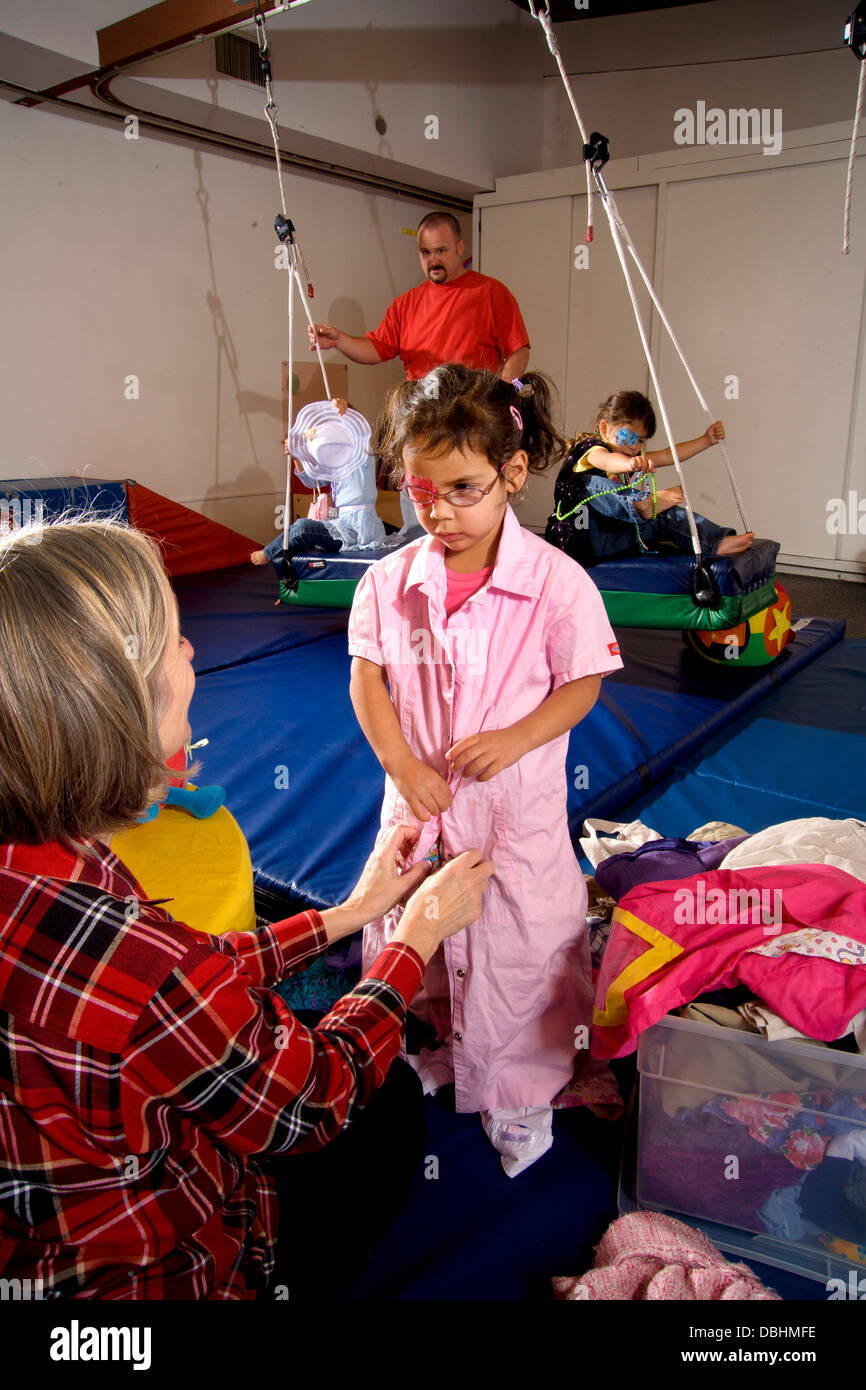 Partially blind girls don costumes for dress-up during an occupational skills class at the Blind Children's - Stock Image