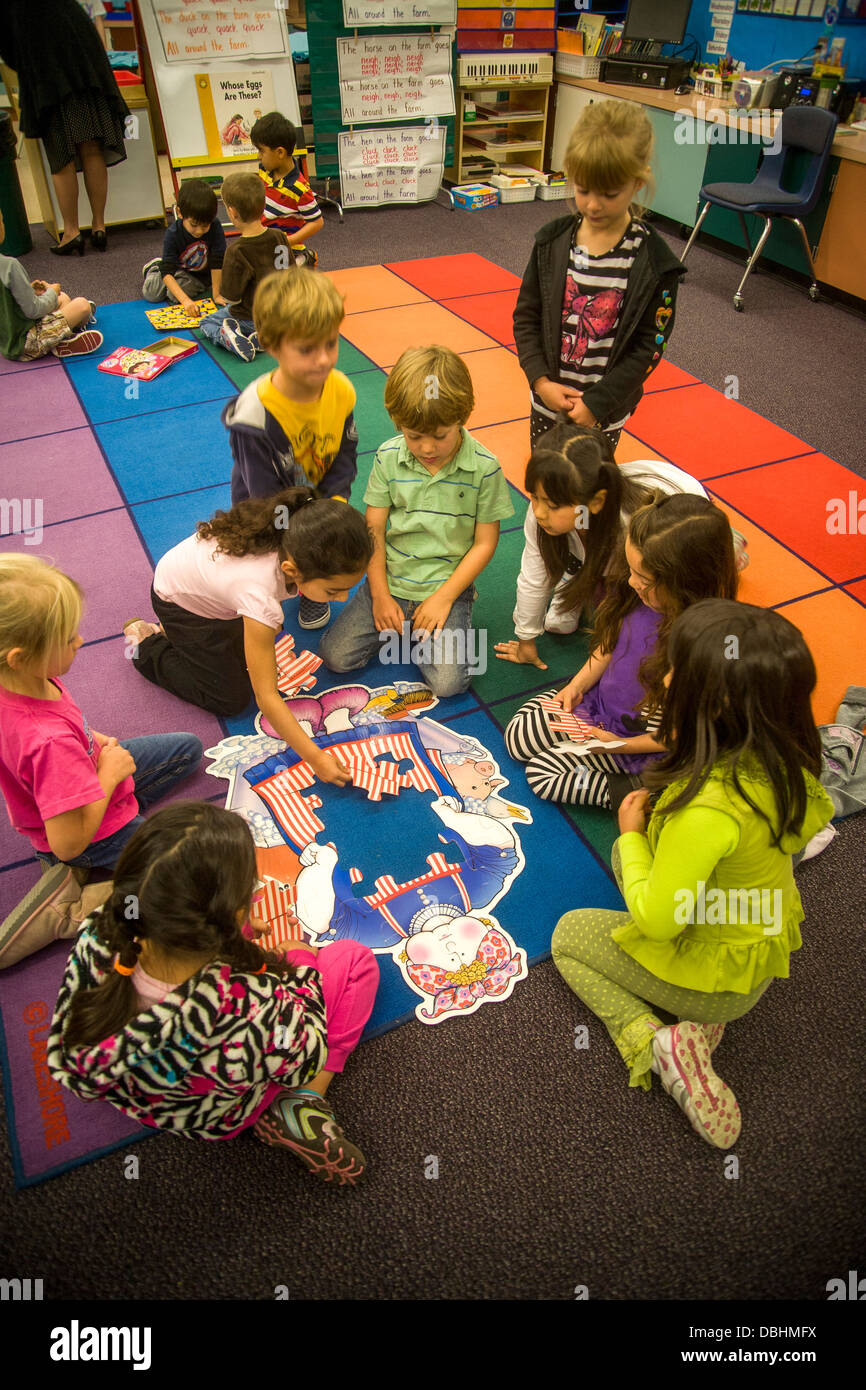 On a classroom floor, a group of kindergarten children collaborate to assemble a jigsaw puzzle in San Clemente, - Stock Image